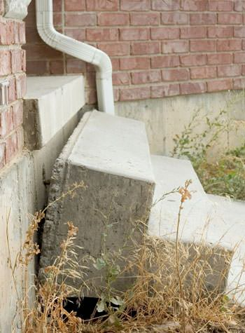 sinking outdoor concrete steps showing cracking and soil washout in Lolo